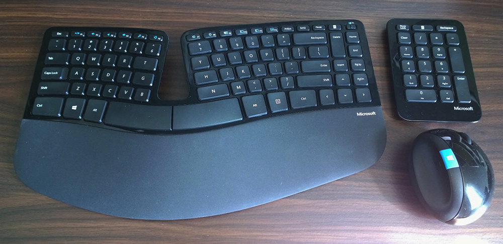 a Microsoft Sculpt keyboard, numpad, and mouse on a desk
